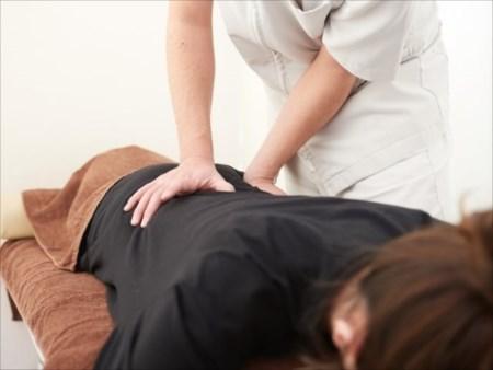 大阪府で骨盤矯正をお考えなら自分に合った施術が受けられる整体へ-【ウェルネスセラピー】がお客様の体の状態に合わせそれに適した施術を行います-骨盤矯正の施術を行ってもらっている女性の画像